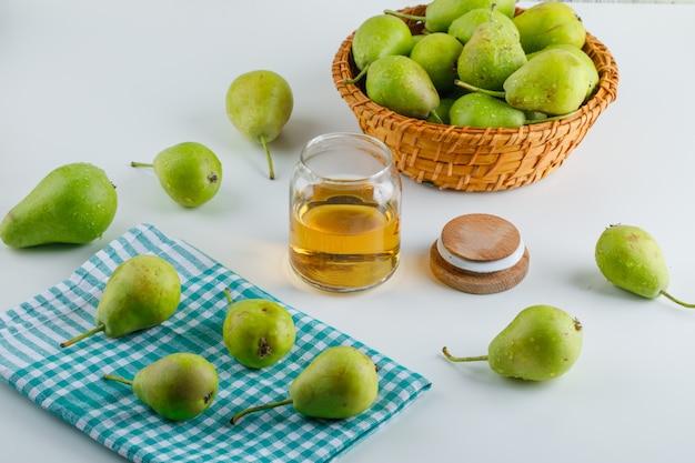 Pere in un cestino con la vista dell'angolo alto del miele su bianco e sul tovagliolo di cucina