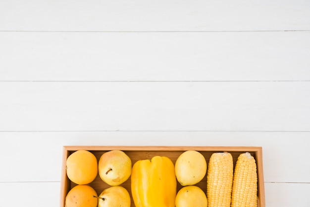 Pears; bell pepper and corn on wooden tray over the white table