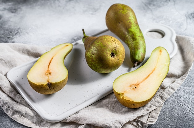 Pears on a ceramic cutting board.