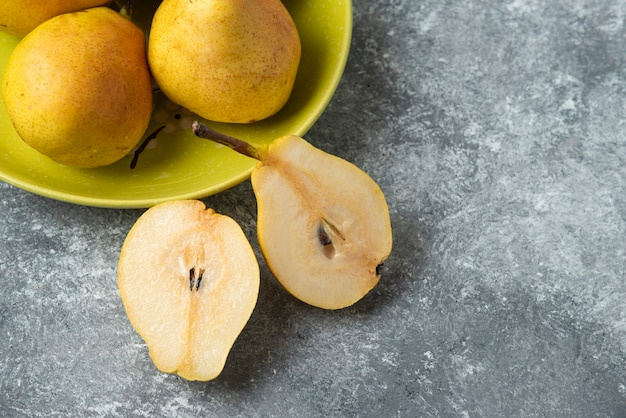 梨はコンクリートの表面で半分にカットされます。 無料写真