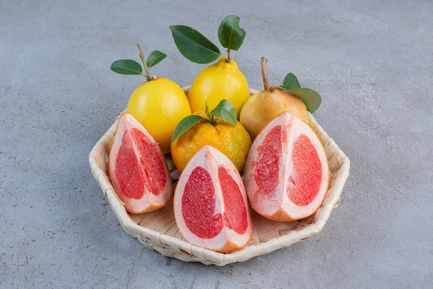 Pears and grapefruit slices in a white basket on marble background.
