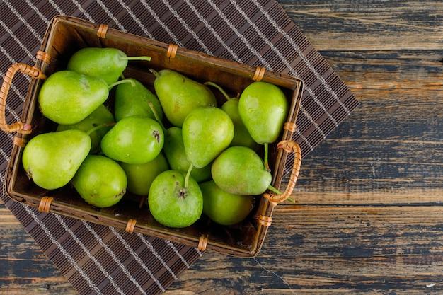 Груши в корзине на деревянном и столовом столе. плоская планировка