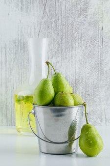 Груши в мини-ведре с травяным напитком на белой и шероховатой стене