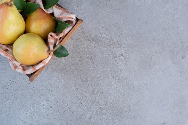 梨、葉、大理石の背景に木製のバスケットのタオル。