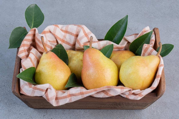 Pears, leaves and a towel in a wooden basket on marble background.