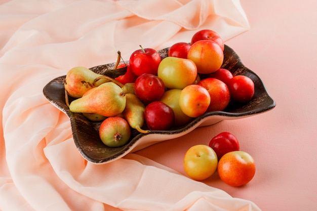 Pears and plums in a plate on pink and textile background. high angle view.