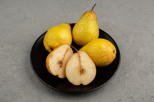 Pears ripe sliced and whole inside black plate and on a bright desk