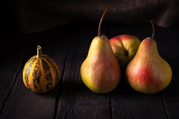 Pears and a small pumpkin on a wooden table in the village.