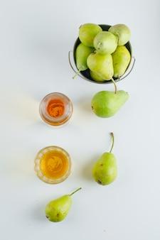 白い表面、上面にミニバケツで飲み物と梨。