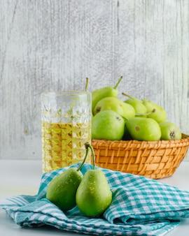 Груши с напитком, кухонное полотенце в корзине на белой и шероховатой стене