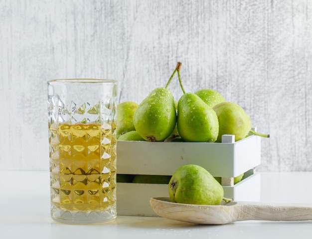 Pears with drink in a wooden box and spoon on white and grungy wall, side view.