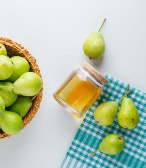 Pere con miele in un cestino sull'asciugamano di cucina e bianco, disposizione piana.