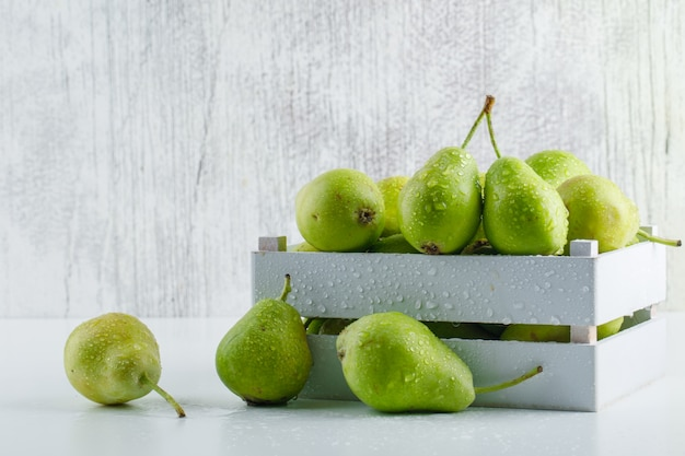 Pears in a wooden box side view on white and grungy background