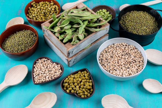 Peas and beans in wooden box, bowls with spoons
