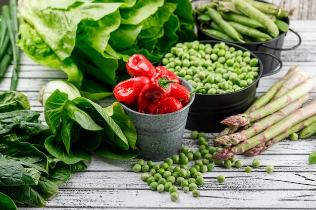 Peas, green pods in saucepans with lettuce, peppers, asparagus, sorrel, bok choy, green onion high angle view on a grungy wooden wall