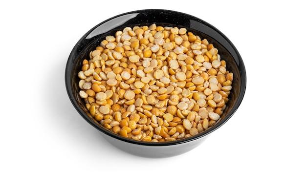 白い背景で隔離の黒いボウルのエンドウ豆。高品質の写真