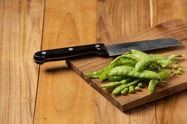 Peas laid on a chopping board on a wooden table