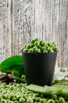 Peas in a mini bucket with bok choy, green pods, asparagus side view on a wooden grunge wall