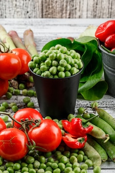 Peas in a mini bucket with peppers, tomatoes, asparagus, bok choy, green pods high angle view on a grungy wooden wall