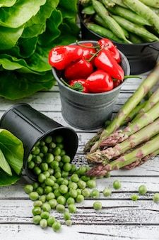 Peas and peppers in buckets with lettuce, green pods, asparagus, bok choy high angle view on a wooden wall