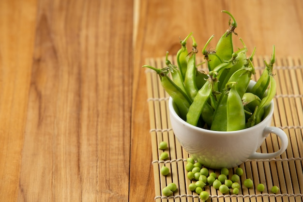 Peas placed in a cup on a wooden table