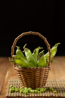 Peas placed in a woven wooden basket on a wooden table