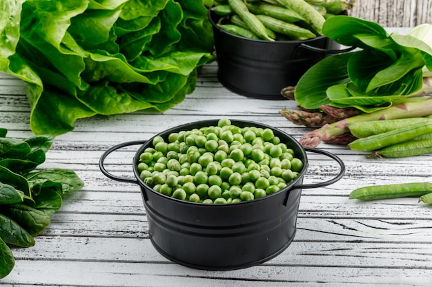 Peas in a saucepan with asparagus, sorrel, bok choy, lettuce, green pods high angle view on a wooden wall