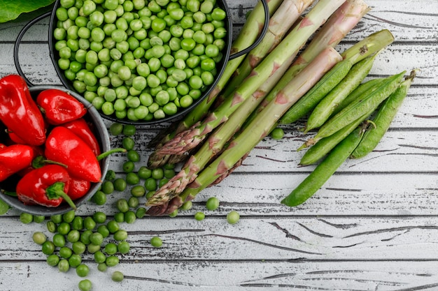 Peas in a saucepan with peppers, asparagus, green pods top view on a wooden wall