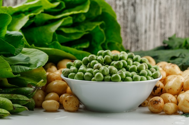 Peas with green pods, spinach, sorrel, lettuce in a bowl on white and grungy wall, side view.