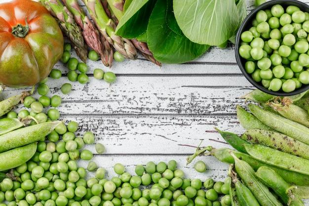 Горох с помидорами, бок чой, зеленые стручки, спаржа в ведре на деревянной стене, плоская планировка.