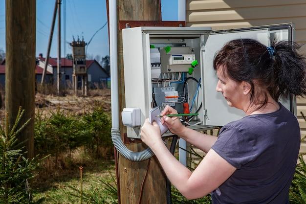 Крестьянка снимает показания электросчетчика.