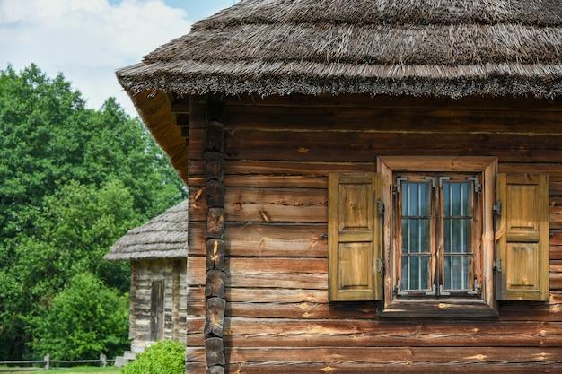 Крестьянский деревянный дом с соломенной крышей.