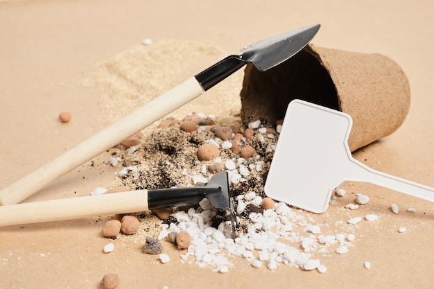 Торфяной горшок, лопаты и грабли, почвенные добавки и удобрения на крафт-бумаге, место для копирования, концепция садоводства, время для посадки семян и саженцев