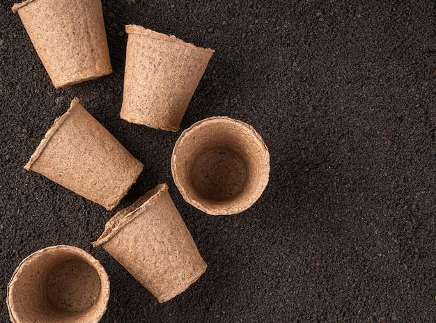 Торфяные горшки на коричневой почве концепция выращивания