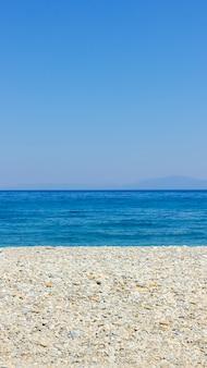 Галечный пляж и голубое небо. жизненный баланс и гармония. концепция летних каникул. минимализм