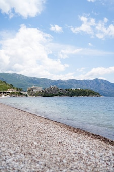 Pebble beach by the sea with views of green mountains and buildings