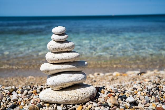 Галечный пляж с балансирующим крупным планом каменной пирамиды. концепция спокойствия и баланса. размытый фон.