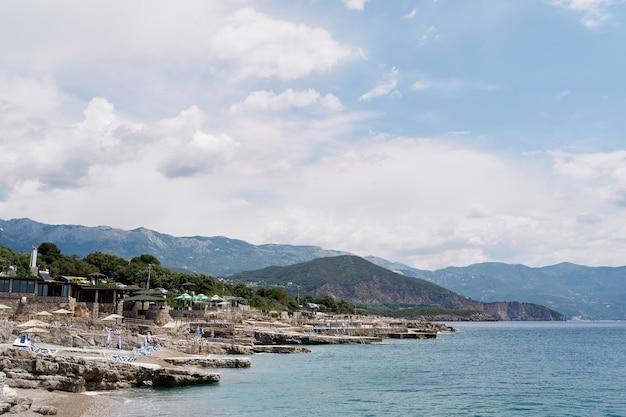 Галечный пляж с каменными выступами у моря