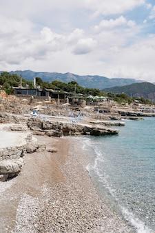 Галечный пляж с каменными выступами, шезлонгами, зонтиками и небольшим рестораном.