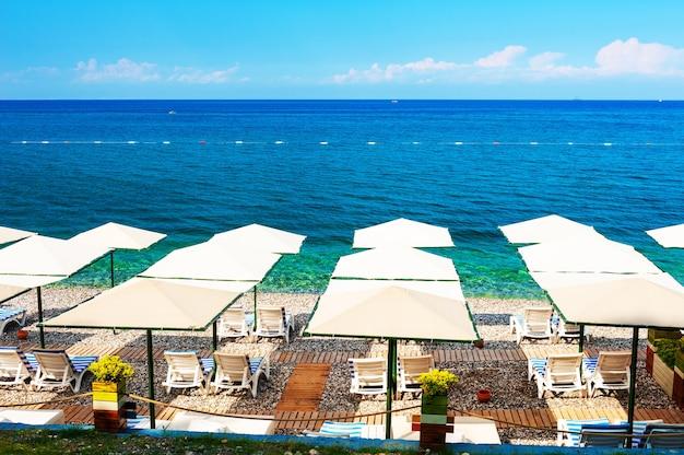 Галечный пляж с зонтиками в кемере, турция. красивый летний пейзаж. концепция туристического направления