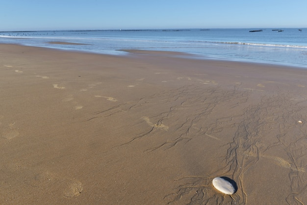 Галька на мокром песке на пляже на фоне моря в атлантическом океане во франции