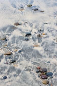 모래 해변과 돌에 조약돌