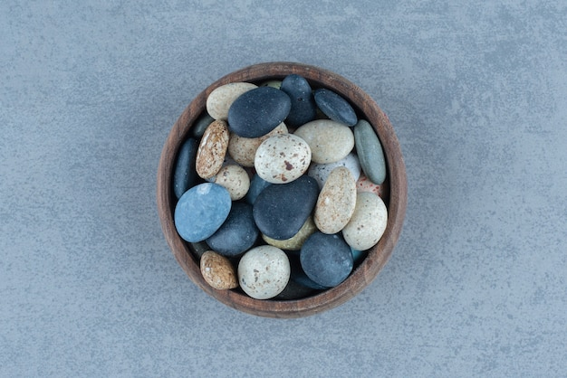 Pebble stone candies in a bowl, on the marble table.