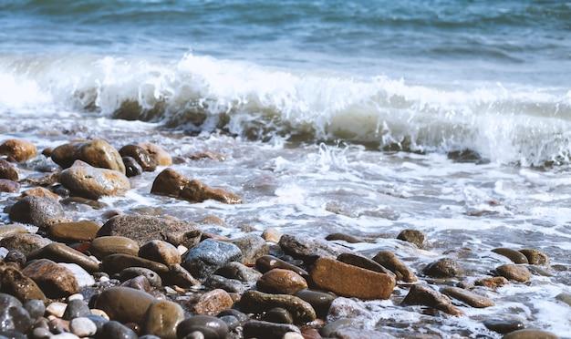 Галька у моря. шелковисто-синие морские волны