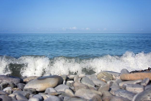 해안의 자갈 돌은 흐릿한 거리 배경에서 닫힙니다. 자연 배경입니다.