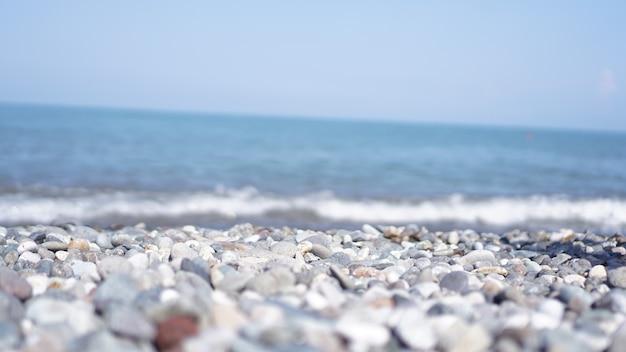 해안에 있는 자갈 돌들은 먼 배경의 흐릿한 빛에 닫힙니다. 선택적 초점