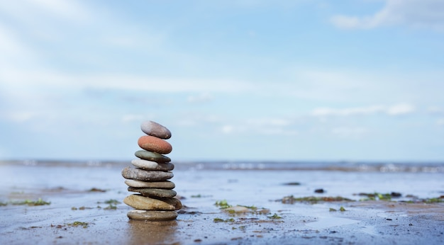 Pebble tower by seaside with blurry seascape, stack of zen rock stones on the sand, stones pyramid on the beach symbolizing, stability, harmony balance with shallow depth of field.