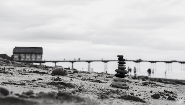 Галечная башня на берегу моря с размытым причалом, спускающимся к морю