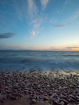파도와 놀라운 하늘과 함께 해변을 따라 자갈.