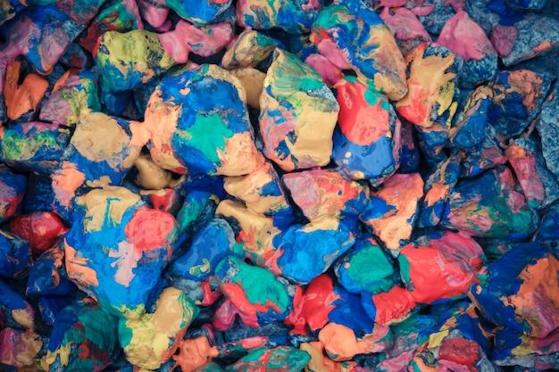小石は明るい色のペンキを塗った。さまざまな色で覆われた石の表面。抽象的な平らな線の背景。